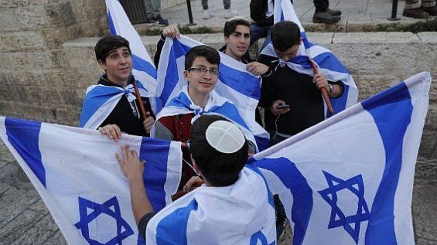 شبان يهود يحملون العلم الإسرائيلي خلال مسيرة للاحتفال ب'يوم القدس' في ذكرى توحيد المدينة خلال حرب 1967، 13 مايو 2018 (Thomas COEX/AFP)
