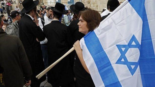 امرأة تحمل العلم الإسرائيلي خلال مسيرة للاحتفال ب'يوم القدس' في ذكرى توحيد المدينة خلال حرب 1967، 13 مايو 2018 (Thomas COEX/AFP)