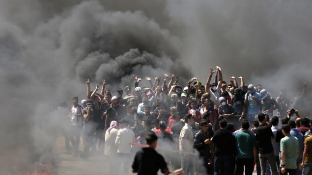 متظاهرو فلسطينيون يحرقون الإطارات بالقرب من الحدود بين إسرائيل وغزة، شرقي مدينة غزة، 14 مايو، 2018.   (AFP PHOTO / MAHMUD HAMS)
