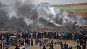 متظاهرون فلسطينيون ينظرون إلى الغاز المسيل للدموع والدخان المتصاعد من إطارات محترقة، شرقي مدينة غزة في 14 مايو، 2018.  (AFP PHOTO / Mohammed ABED)