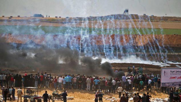 متظاهرون فلسطينيون ينظرون إلى الغاز المسيل للدموع والدخان المتصاعد من إطارات محترقة، شرقي مدينة غزة في 14 مايو، 2018 (AFP PHOTO / Mohammed ABED)