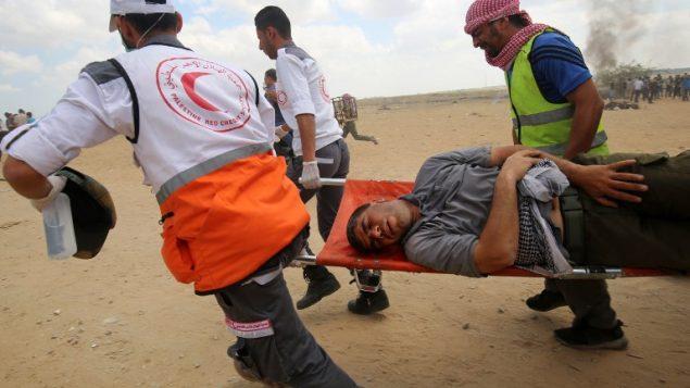 فلسطينيون يحملون متظاهرا مصابا خلال موجهات مع القوات الإسرائيلية عند الحدود بين قطاع غزة وإسرائيل، شرقي مدينة خان يونس، 14 مايو، 2018. ( AFP PHOTO / SAID KHATIB)