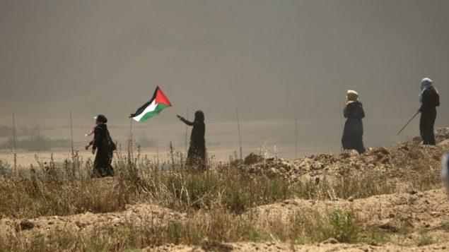 نساء فلسطينيات يوحن بالعلم الفلسطيني خلال مواجهات مع القوات الإسرائيلية بالقرب من الحدود بين قطاع غزة وإسرائيل، شرقي مدينة غزة، 14 مايو، 2018.  (AFP PHOTO / MAHMUD HAMS)