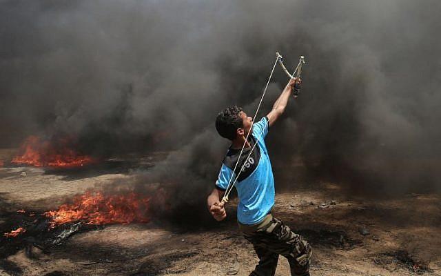 شاب فلسطيني يستخدم المقلاع خلال مواجهات مع القوات الإسرائيلية بالقرب من حدود غزة وإسرائيل شرقي مدينة خان يونس، 14 مايو، 2018. (AFP PHOTO / SAID KHATIB)