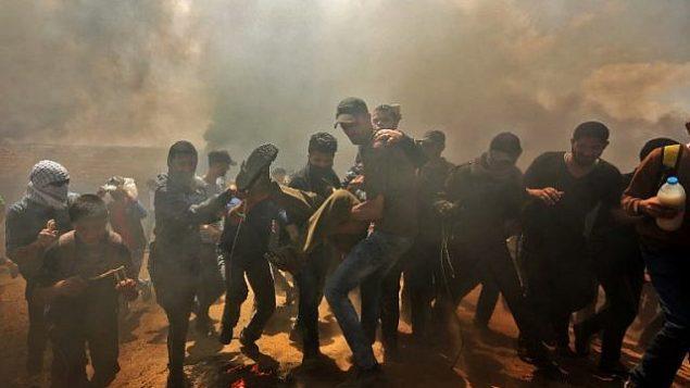فلسطينيون يحملون متظاهرًا جريحًا خلال مواجهات مع القوات الإسرائيلية بالقرب من الحدود بين قطاع غزة وإسرائيل شرق مدينة غزة يوم 14 مايو 2018. (MAHMUD HAMS / AFP)