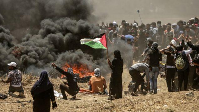 امرأة من غزة تحمل العلم الفلسطيني امام  اشتباكات بين فلسطينيين والجيش الإسرائيلي بالقرب من الحدود بين قطاع غزة وإسرائيل  14 مايو / أيار 2018 يوم تدشين السفارة الأمريكية في القدس MAHMUD HAMS / AFP