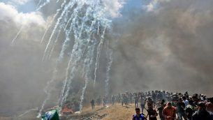 فلسطينيون يحاولون الاختباء من الغاز المسيل للدموع الذي أطلقته القوات الإسرائيلية بالقرب من الحدود بين قطاع غزة وإسرائيل في شرقي مدينة غزة، 14 مايو، 2018. (AFP/ MAHMUD HAMS)