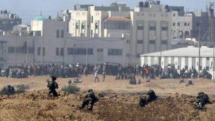 صورة تم التقاطها في 14 مايو، 2018 من كيبوتس ناحال عوز في جنوبي إسرائيل عبر الحدود مع غزة لجنود إسرائيليين ومتظاهرين فلسطينيين يحتشدون بالقرب من السياج الحدودي مع إسرائيل. (AFP/JACK GUEZ)