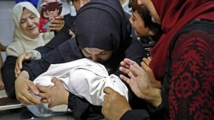 والدة ليلى الغندور، طفلة رضيعة فلسطينية تبلغ من العمر 8 أشهر التي توفيت جراء استنشاقها للغاز المسيل للدموع، بحسب وزارة الصحة التابعة لحركة حماس في غزة، تختضن جثة طفلتها في مكان حفظ الجثث في مستشفى 'الشفاء' في مدينة غزة في 15 مايو، 2018. في 16 مايو، قالت الوزارة إنه لم يتم تحديد سبب الوفاة بصورة قاطعة. (AFP/Thomas Coex)