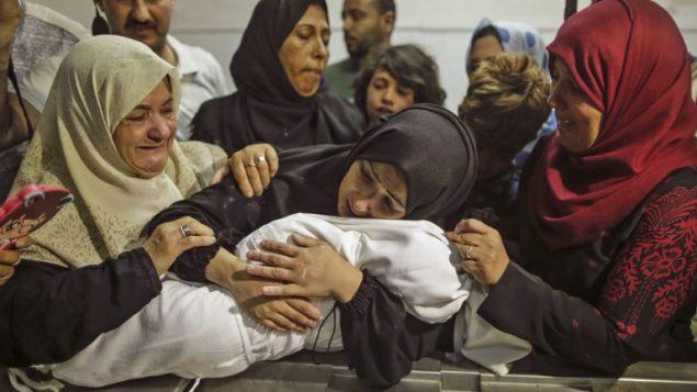 والدة ليلى الغندور تحملها في مشرحة مستشفى الشفا في غزة، 15 مايو 2018 (AFP / MAHMUD HAMS)