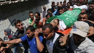 المشيعون يحملون جثمان الشاب الفلسطيني محمد دويدر (27 عاما)، الذي قُتل خلال مواجهات على الحدود بين غزة وإسرائيل في اليوم السابق، خلال جنازته في مخيم النصيرات في قطاع غزة، 15 مايو، 2018.  (AFP PHOTO / MOHAMMED ABED)
