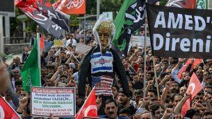 متظاهرون يحملون دمية للرئيس الأمريكي دونالد ترامب ويهتفون شعارات في ديار بكر في تركيا، 15 مايو، 2018. (AFP / ILYAS AKENGIN)