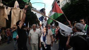 فلسطينيون يسكنون في تيسالونيكي اليونانية يحرقون العلم الامريكي والإسرائيلي امام القنصلية الامريكية خلال مظاهرة لادانة سفك الدماء عند حدود غزة ونقل السفارة الامريكية الى القدس، 17 مايو 2018 (AFP/Sakis MITROLIDIS)