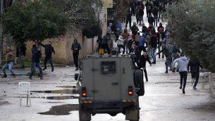 صورة توضيحية: شبان فلسطينيون يرشقون حجارة باتجاه قوات الامن الإسرائيلية خلال عملية عسكرية في مدينة جنين في الضفة الغربية، 18 يناير 2018 (AFP/Jaafar Ashtiyeh)