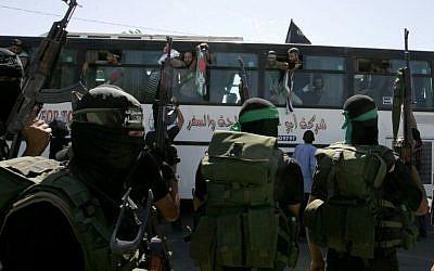 توضيحية: أعضاء في حركة حماس يستقبلون حافلة تقل أسرى فلسطينيين تصل إلى معبر رفح مع مصر في جنوب قطاع غزة، 18 أكتوبر، 2011. (Abed Rahim Khatib/Flash 90)