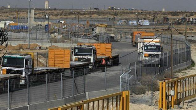 شاحنات فارغة من غزة تنتظر شحنها محملة بالبضائع (يسارًا) مع مرور شاحنات كاملة باتجاه غزة في الخلفية عند معبر كيرم شالوم بين إسرائيل وغزة في العام الماضي. (Tsafrir Abayov/Flash90)