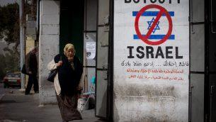امرأة فلسطينية تمر من أمام  رسم على جدار يدعو إلى مقاطعة إسرائيل في أحد شوارع مدينة بيت لحم في الضفة الغربية، 11 فبراير، 2015. (Miriam Alster/Flash 90)