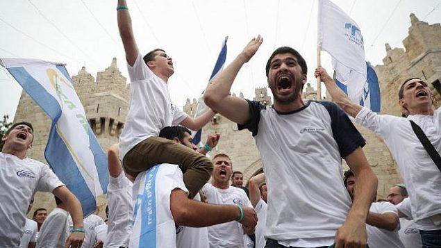 الاف اليهود يلوةحون بالاعلام الإسرائيلية خلال الاحتفال ب'يوم القدس' في مسيرة تمر بباب العامود في البلدة القديمة في القدس بطريقهم الى حائط المبكرى، 13 مايو 2018 (Yonatan Sindel/Flash90)