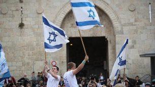 الاف اليهود يلوحون بالاعلام الإسرائيلية خلال الاحتفال ب'يوم القدس' في مسيرة تمر بباب العامود في البلدة القديمة في القدس بطريقهم الى حائط المبكى، 13 مايو 2018 (Yonatan Sindel/Flash90)