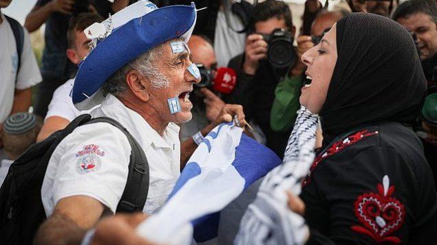 رجل يهودي يحمل علم اسرائيلي يتشاجر مع امرأة عربية مع احتفال الالاف ب'يوم القدس' في ذكرى توحيد المدينة خلال حرب 1967، 13 مايو 2018 (Yonatan Sindel/Flash90)