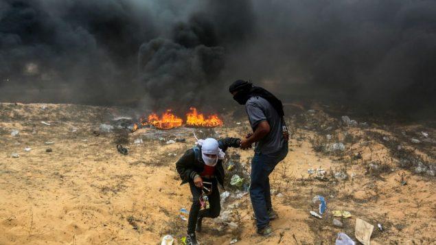 متظاهرون فلسطينيون خلال اشتباكات مع القوات الإسرائيلية بالقرب من الحدود بين اسرائيل وقطاع غزة في رفح، 14 مايو 2018 (Abed Rahim Khatib/Flash90)