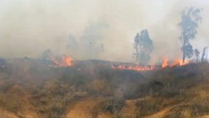 دخان وألهبة النار تتصاعد من أراض عشبية في كيبوتس بئيري في جنوب إسرائيل بعد أن قام الفلسطينيين بتطيير طائرة ورقية محملة بزجاجة حارقة عبر الحدود في 2 مايو، 2018.  (Screen capture/Rafi Bavian)