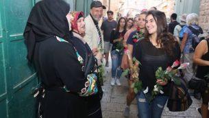 """خلال مسيرة للسلام نظمتها منظمة """"تاغ مئير"""" شابة توزع ورودا على أصحاب متاجر عرب في البلدة القديمة في القدس قبيل 'مسيرة العلم'، 24 مايو، 2017.  (Courtesy)"""
