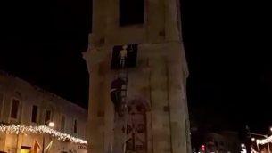 ناشطان من منظمة 'عوتسما يهوديت' يقومون بتعليق صورة لمنفذ هجوم على برج الساعة في يافا.  (لقطة شاشة: Ynet news)