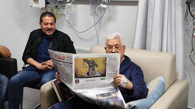 رئيس السلطة الفلسطينية محمود عباس يتماثل إلى الشفاء في المستشفى ويقرأ صحيفة يظهر على صفحتها الأخيرة رسم كاريكاتير لجندي إسرائيلي يقوم بتسميم طفلة فلسطينية، 22 مايو، 2018. (وكالةالأنباء الفلسطينية 'وفا')