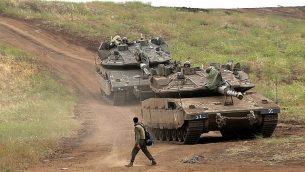 جندي إسرائيلي يقف بجانب دبابتين من طراز 'ميركافا علامة 4' في هضبة الجولان خلال مناورة عسكرية في 7 مايو، 2018.  (AFP PHOTO / JALAA MAREY)