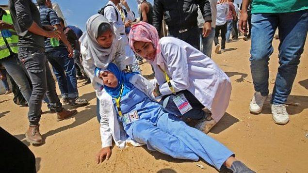 رزان النجار (من اليمين)، مسعفة فلسطينية تبلغ من العمر 21 عاما تقدم الإسعاف لإحدى زميلاتها التي أصيبت خلال مواجهات بالقرب من الحدود مع إسرائيل، شرقي خان يونس في جنوب قطاع غزة، 15 مايو، 2018.  (AFP/ SAID KHATIB)