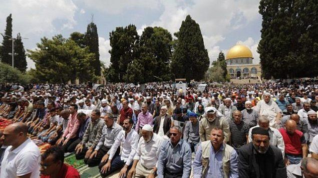 يصلي المسلمين بالقرب من قبة الصخرة والمسجد الأقصى، خلال صلاة الجمعة الثالثة من شهر رمضان المبارك في 1 يونيو 2018. (AFP Photo/Ahmad Gharabli)