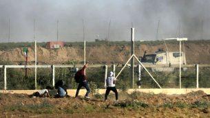 رجل فلسطيني يرمي حجرا باتجاه القوات الإسرائيلية خلال مظاهرة عند حدود غزة، 1 يونيو 2018 (AFP/ Mahmud Hams)