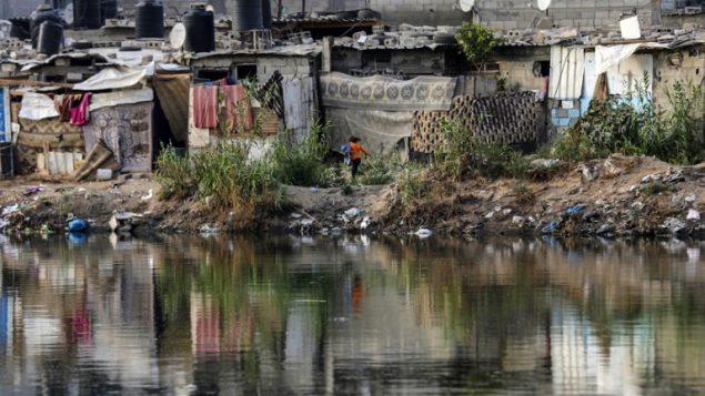 اكواخ بالقرب من بركة مياه صرف في حي فقير في مدينة غزة، 1 يونيو 2018 (AFP/Mahmud Hams)