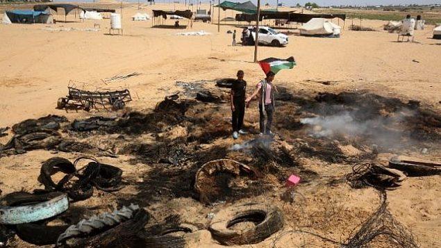 فلسطينيون يتفحصون كومة من الإطارات تشير التقارير إلى أن الطائرات الإسرائيلية اشعلت فيها النيران بالقرب من الحدود مع إسرائيل شرق رفح جنوب قطاع غزة، قبيل المواجهات الأسبوعية في 8 يونيو / حزيران 2018. (AFP Photo / Said Khatib)