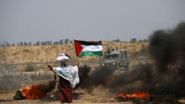 امرأة فلسطينية ترفع العلم الفلسطيني امام السياج الحودي مع اسرائيل، الى جانب إطارات مشتعلة، شرقي خان يونس، 8 يونيو 2018 (AFP/ SAID KHATIB)