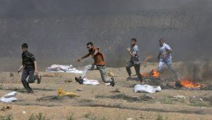صورة توضيحية: فلسطينيون يركضون بالقرب من السياج الشائك مع إسرائيل خلال اشتباكات في أعقاب مظاهرة على طول الشريط الحدودي مع قطاع غزة شرق مدينة غزة في 8 يونيو  2018. (AFP PHOTO / MAHMUD HAMS)