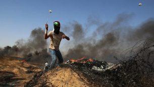 شاب فلسطيني يستخدم مقلاع لإلقاء الحجارة على القوات الإسرائيلية خلال اشتباكات قرب الحدود مع إسرائيل، شرق خان يونس في جنوب قطاع غزة في 8 يونيو  2018. (Said Khatib/AFP)