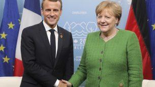 الرئيس الفرنسي فرانسوا ماكرون يلتقي بالمستشارة المانية انغيلا ميركل على هامش قمة السبع في كيبيك، كندا، 8 يونيو 2018 (Ludovic MARIN / POOL / AFP)