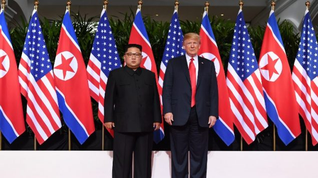 الرئيس الأمريكي دونالد ترامب (من اليمين) والرئيس الكوري الشمالي كيم جونغ أون (من اليسار) في بداية قمتهما التاريخية، في فندق 'كابيلا' في جزيرة سنتوسا في سنغافورة، 12 يونيو، 2018.(AFP PHOTO / SAUL LOEB)