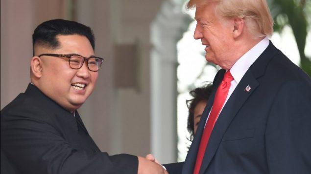 مصافحة بين الرئيس الأمريكي دونالد ترامب من اليمين) وزعيم كوريا الشمالية كيم جونغ أون خلال لقائهما في مستهل القمة الأمريكية -الكورية الشمالية التاريخية  التي جمعتهما في فندق 'كابيلا' في جزيرة سنتوسا في سنغافورة، 12 يونيو، 2018. AFP PHOTO / SAUL LOEB