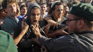 اشتباكات بين متظاهرين وعناصر الشرطة في بؤرة نتيف هأفوت الاستيطانية في الضفة الغربية، 12 يونيو 2018 (MENAHEM KAHANA/AFP)
