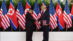 زعيم كوريا الشمالية كيم جونغ أون (من اليسار) والرئيس الأمريكي دونالد ترامب (من اليمين) يتصافحان خلال مشاركتهما في مراسم توقيع في نهاية القمة الأمريكية-الكورية الشمالية التاريخية التي جمعتهما في فندق 'كابيلا' في جزيرة سنتوسا في سنغافورة، 12 يونيو، 2018.  (AFP PHOTO / POOL / Anthony (WALLACE