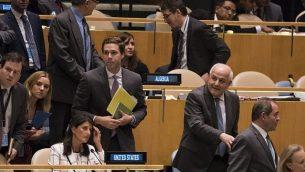 السفير الفلسطيني لدى الأمم المتحدة رياض منصور (الشعر الأبيض) يمر من جانب السفيرة الأمريكية لدى الأمم المتحدة نيكي هايلي (الجالسة على الكرسي) خلال عملية تصويت لإدانة الأنشطة الإسرائيلية في غزة، في الجمعية العامة للأمم المتحدة في نيويورك، 13 يونيو، 2018. (AFP PHOTO / Don EMMERT)