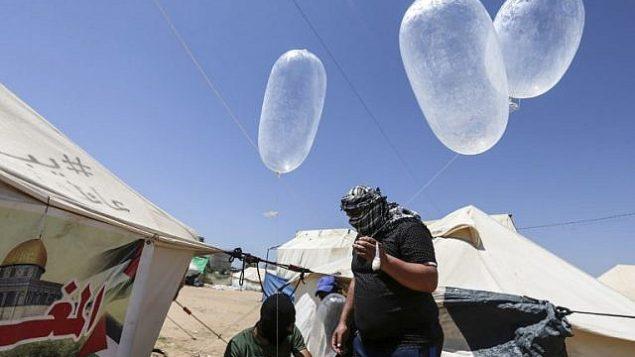 محتجون فلسطينيون يعدون طائرات ورقية محملة بمواد حارقة لإطلاقها باتجاه إسرائيل، ، عند حدود غزة إسرائيل في البريج، وسط قطاع غزة، 14 يونيو، 2018.  (AFP/Mahmud Hams)