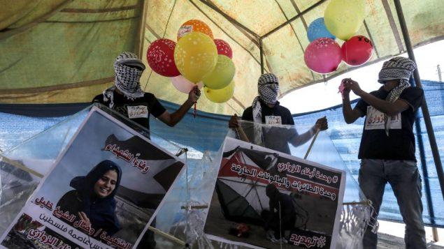 محتجون فلسطينيون يعدون بالونات محملة بمواد حارقة لإطلاقها باتجاه إسرائيل، عند حدود غزة إسرائيل في البريج، وسط قطاع غزة، 14 يونيو، 2018.  (AFP/Mahmud Hams)