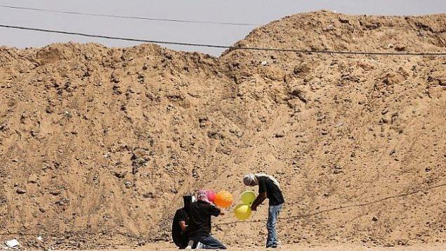 غزيون يعدون بالونات محملة بمواد حارقة لإطلاقها باتجاه إسرائيل، عند حدود غزة في البريح بوسط قطاع غزة، 14 يونيو، 2018. (AFP/ MAHMUD HAMS)