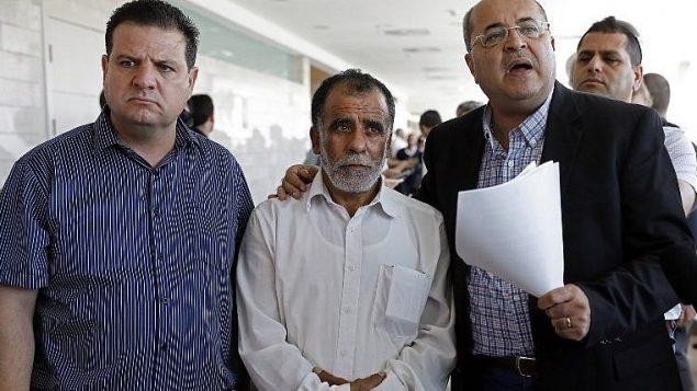 حسين دوابشة (مركز)، جد الرضيع الفلسطيني الذي قُتل في هجوم حريق مع والديه في منزلهم في بلدة دوما، مع اعضاء الكنيست العرب ايمن عودة واحمد طيبي خلال محكمة المشتبه بهما اليهوديان بنفيذ الهجوم، 19 ونيو 2018 (AFP / AHMAD GHARABLI)