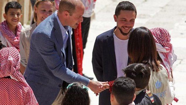 الأمير وليام البريطاني وولي العهد الأردني حسين بن عبدالله يتحدثان مع اطفال سوريين واردنيين خلال زيارة لموقع جرش الاثري، 25 يونيو 2018 (AFP PHOTO/AHMAD ABDO)