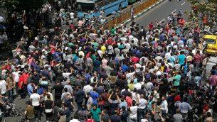 متظاهرون إيرانيون يرفعون شعارات خلال مظاهرة بوسط طهران في 25 يونيو عام 2018. نظم التجار في سوق البازار الكبير بالعاصمة الإيرانية إضرابا نادرا احتجاجا على انهيار الريال في سوق الصرف الأجنبي مع خروج المتظاهرين أيضا إلى الشوارع. (ATTA KENARE / AFP)